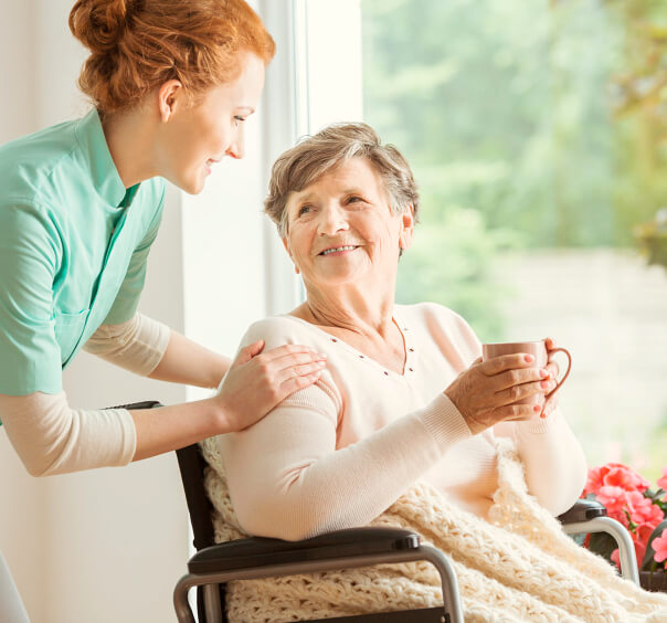 caregiver and elder woman drinking coffee