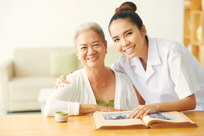 caregiver and elder woman smiling