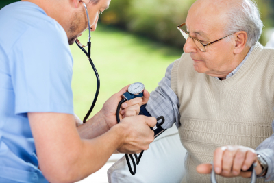 male nurse checking blood pressure of senior man